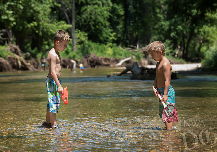 NWA Democrat Gazette/SPENCER TIREY Cade Chesnutt, 6, right, and Zander Osborn, 7,  look for fish  while playing  Monday Jul10, 2017, in the McKisic Creek near Lake Bella Vista. The boys where out with their grandmothers enjoying the nice weather.