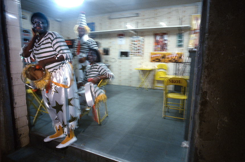 ?After their appearance, clown-costumed dancers from Mocidade Independente de Padre Miguel stop at a corner bar to rest. The hour-and-a-half-long parades drain even the most enthusiastic samba dancers.