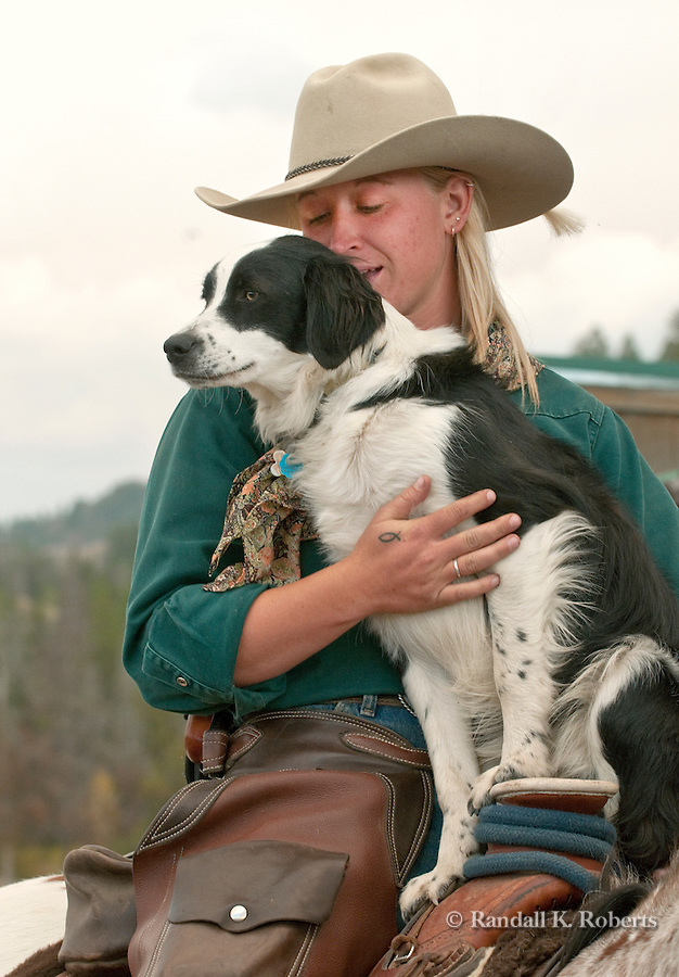 Wrangler Jesi DeVries gives Chance the ranch dog a better view of the corral at Triangle X Dude Ranch, Grand Teton National Park, Wyoming