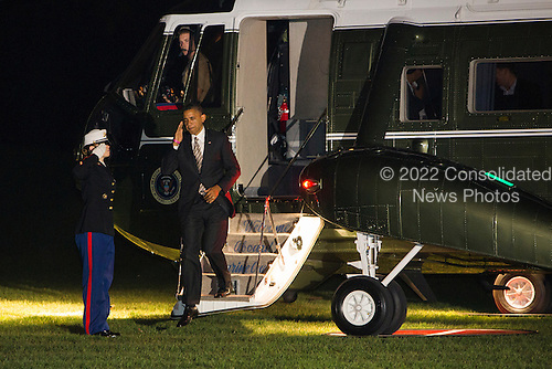 United States President Barack Obama salutes the Marine Guard as he walks down the steps from Marine One on the South Lawn of the White House in Washington, D.C. after returning home from a series of campaign events across the country on October 25, 2012. .Credit: Kristoffer Tripplaar  / Pool via CNP