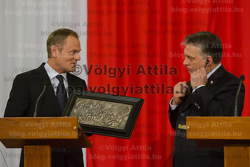Donald Tusk (L) prime minister of Poland gives a present to his counterpart Viktor Orban (R) Prime Minister of Hungary during a press conference in Budapest, Hungary on January 29, 2014. ATTILA VOLGYI
