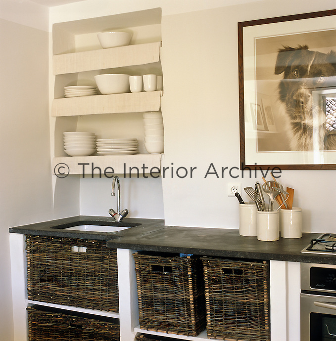 The kitchen has simple but effective storage with recessed wall shelves and wicker baskets underneath the stone work surface