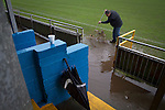 A groundsman sweeping away surface water from the pitch surround before Port Talbot Town played host to Caerau Ely in a Welsh Cup fourth round tie at the Genquip Stadium, formerly known as Victoria Road. Formed by exiled Scots in 1901 as Port Talbot Athletic, they competed in local and regional football before being promoted to the League of Wales  in 2000 and changing their name to the current version a year later. Town won this tie 3-0 against their opponents from the Welsh League, one level below the welsh Premier League where Port Talbot competed, watched by a crowd of 113.