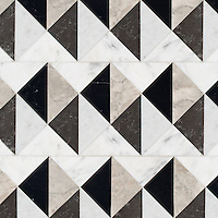 Arbus, a hand-cut stone mosaic, shown in polished Soccoro Grey, Nero Marquina, Carrara, and honed Cavern, is part of the Palazzo® collection by New Ravenna.