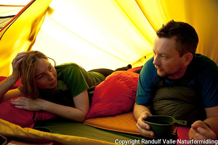 Mann og dame slapper av i telt. ---- Man and woman relaxing in tent.