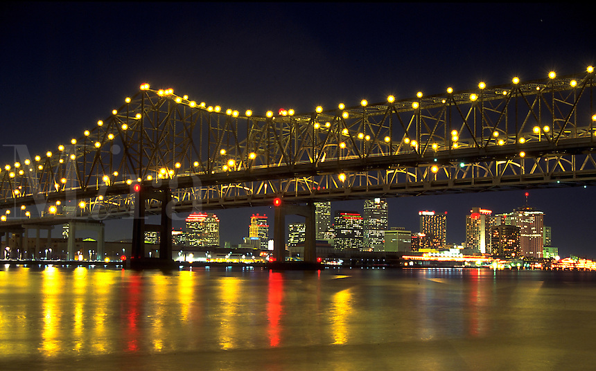 Scenic evening view of the Mississippi River Bridge and New Orleans city skyline with lights reflected in the water. New Orleans, Louisiana.