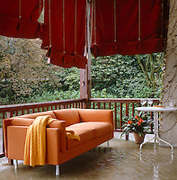 Red Roman blinds provide shade on this tiled terrace which is furnished with a modern orange sofa