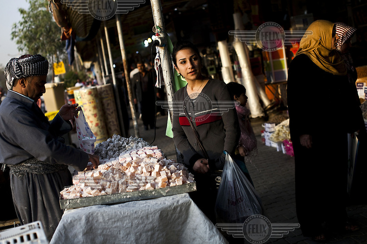 A woman buys sweets from a stall at a street market in Erbil, Iraqi Kurdistan.