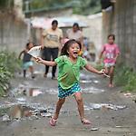 A girl runs through the streets in Pulilan, a village in Bulacan, Philippines, where the Kapatiran-Kaunlaran Foundation (KKFI) sponsors a preschool. <br /> <br /> KKFI is supported by United Methodist Women.