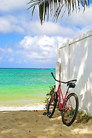 Graceful in repose, a bicycle rests against a white fence, beneath a palm frawn in the inviting sands and waters near Lanikai Beach on Oahus windward side.