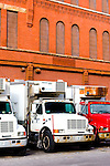 Several refrigerated trucks are lined up on the docks of a warehouse in the meat packing district of Chicago.