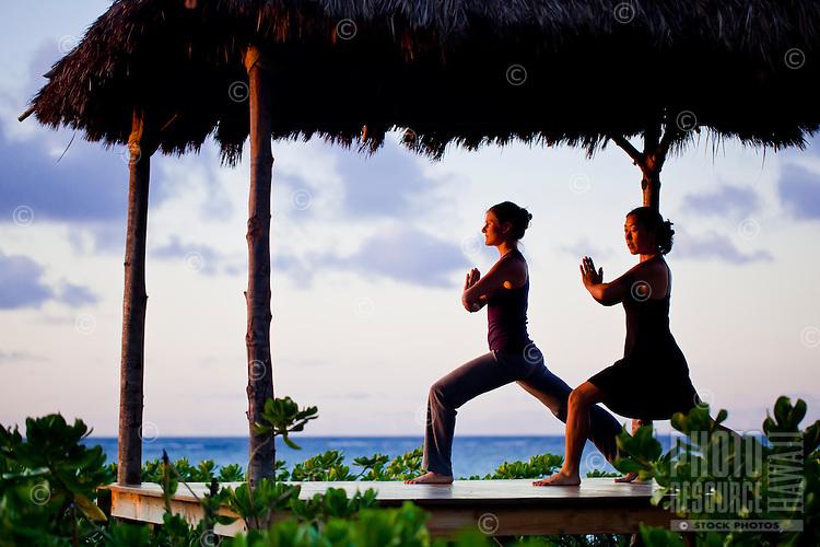 Women practicing yoga postures in a beachfront gazebo