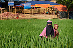 A Rohingya woman carries a child as she walks through a rice field in the Mainerghona Refugee Camp near Cox's Bazar, Bangladesh, on October 27, 2017. Since August more than 600,000 Rohingya have fled government-sanctioned violence in Myanmar for safety in Bangladesh.