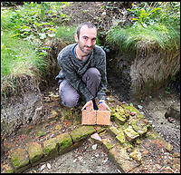BNPS.co.uk (01202 558833)<br /> Pic: PhilYeomans/BNPS<br /> <br /> Present occupant (and direct descendent of Jane Seymour) Dominic Binney with unearthed Tudor tiles in the rediscovered foundations of the Tudor pile. <br /> <br /> Historic Wolf Hall, home to the Seymour family and star of Hilary Mantel's famous trilogy on Henry VIII th, has finally been definitively located after new discoveries around the much smaller ramshackle house that remains today. <br /> <br /> Despite it's fame, nobody really knew where the enormous Tudor pile actually was, or what it looked like, due to its very short but very influential existance in the middle of the tumultuous 16th century.<br /> <br /> Built with a million pound loan (&pound;2,400) from King Henry in 1531, brokered by Thomas Cromwell, the huge house was rapidly brick built in time for the King's pivotal visit with the court and troublesome wife Anne Boleyn in 1535, at which point Sir John Seymour's daughter Jane caught his eye, within a year Anne was dead and Jane, and the rest of the Seymour clan were in.<br /> <br /> They benefitted massively from Royal patronage and the dissolution of the monastries, but it all went wrong when Henry died and the brothers fell out and were later executed in a spectacular fall from power only 21 years after the house was built.<br /> <br /> Historian Graham Bathe and his team have now uncovered part of the outline of the original building, as well as the extensive Tudor brick sewer system that proves the huge scale of the 16th century mansion.