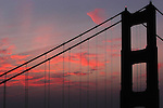 The morning sky is lit up with bright pink clouds with the Golden gate Bridge in the foreground.