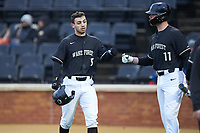 Patrick Frick (5) of the Wake Forest Demon Deacons bumps fists with teammate Shane Muntz (11) after scoring a run during the game against the Illinois Fighting Illini at David F. Couch Ballpark on February 16, 2019 in  Winston-Salem, North Carolina.  The Fighting Illini defeated the Demon Deacons 5-2. (Brian Westerholt/Four Seam Images)