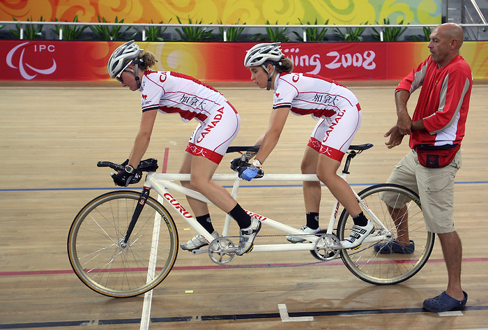 Canadian national team coach Eric Van den Eynde starts off pilot Mathilde Hupin (left) of Bromont, Que. and Genevieve Ouellet of Quebec City at cycling training at the Laoshan Velodrome prior to the Paralympic Games in Beijing, Sep., 3, 2008.  Ouellet is visually impaired. Photo by Mike Ridewood/CPC