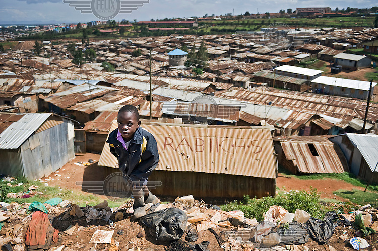 A boy walks along a rubbish strewn roadside. In the background are the rusting, corrugated iron roofs of the Kibera slum.