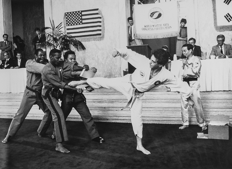 Rep. Mel Levine, D-Calif., breaking two boards with wide side kicks while Master Jhoon Rhee, a martial arts master, watches him on Aug. 2, 1990. (Photo by Maureen Keating/CQ Roll Call)