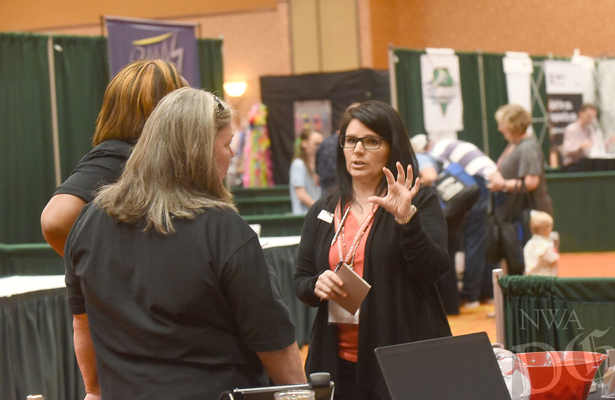 NWA Democrat-Gazette/FLIP PUTTHOFF <br />COUNTY CONFERENCE OPENS<br />Angie Kinard (right) with Telecomp communitcation company talks with conference attendees on Wednesday Aug. 8 2018 during opening day of the Association of Arkansas Counties conference at the John Q. Hammons Center in Rogers. Officials from counties around the state opened the conference Wednesday with vendor exhibits and samples, breakfast and breakout meetings for various posts in county government such as county judges, sheriffs and assessors. The conference continues through Friday. U.S. Rep Steve Womack (R-Rogers) addressed the conference Wednesday. Gov. Asa Hutchinson will speak at 9 a.m. today. Aliyah was at the conference with her grandpa, James Ross of Miller County.