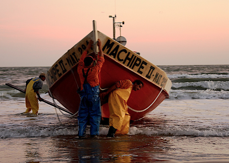 Fishermen hard at work at early hours of the morning in Cabo Polonio, Uruguay.  These town, which dows not offer a dock, requires for an elaborate routine to take the boat from shore and into the water.  It's 6.00am in Cabo Polonio, Rocha, a small beach town in the Atlantic coast of Uruguay. I witness 3 men performing their daily routine. No easy task I have to say.The first lights of dawn are breaking through the doubtful skies, which at times looks hesitant, like wanting to go back to sleep. The wind is blowing hard, harassing the sea into sets of spike white crests.  ...As I approach them in the vast beach, they actively perform the task of precariously sliding the two tons boat through the sand and into the defying ocean.  My presence does not seem to alter in any noticeable way their daily routine, neither the intensity of the task at hand. Two of them, one in each side of the 'Machipe'  manage the ship as it slides over two metal tubes rolling over a set of flat woods used as rails. The third one controls the pace at which the process evolves by lifting or dropping the anchor into the sand. ...The only witness of his role the long line carved in the sand by the heavy weight of the anchor.  Getting 'Machipe' into the sand is only the beginning of what will for sure be a long day of work.