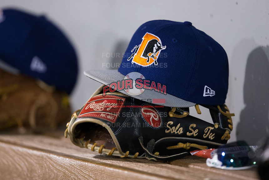 A Durham Bulls cap sits on top of a Rawlings glove in the visitor's dugout during the game against the Charlotte Knights at BB&T BallPark on April 14, 2016 in Charlotte, North Carolina.  The Bulls defeated the Knights 2-0.  (Brian Westerholt/Four Seam Images)