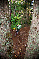 Mountain bikers are seen through the mature hardwood trees on The Flow trail of Copper Harbor Michigan.