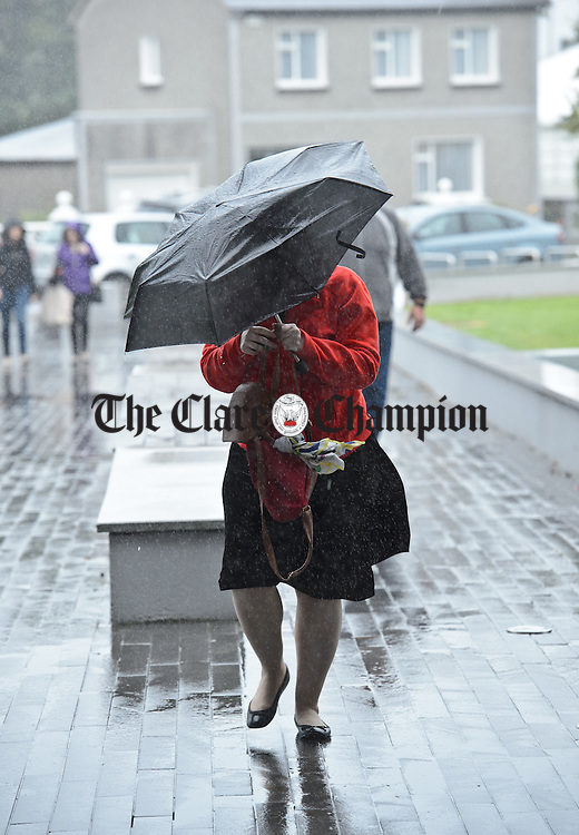A visitor does battle with the weather during Fleadh Cheoil na hEireann in Ennis. Photograph by John Kelly.