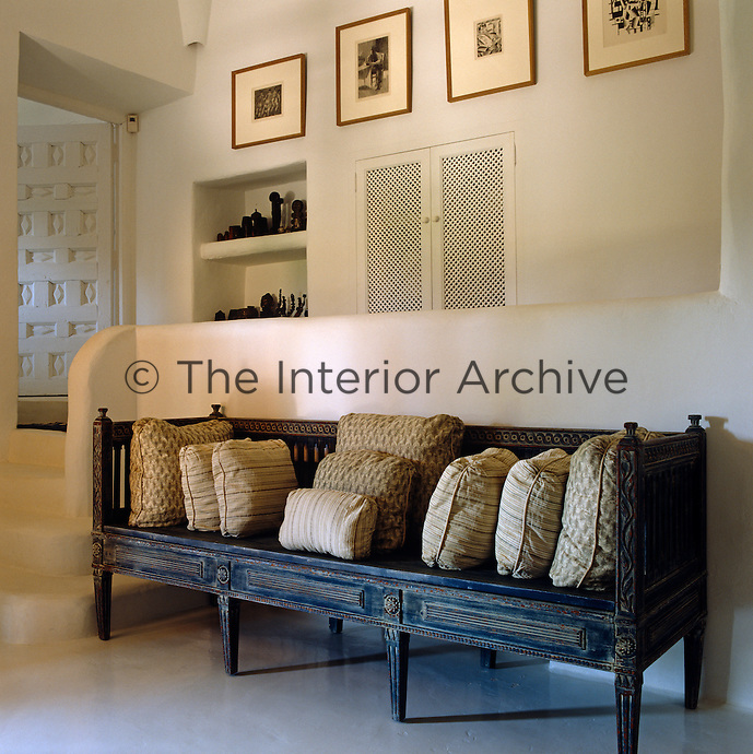An antique painted bench beneath a collection of framed prints in the hallway is filled with cushions