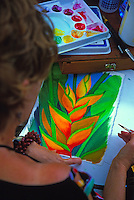 An artist at the Honolulu Zoo Fence in Waikiki's Kapiolani Park paints a tropical heliconia bloom to add to her selection of wares for sale. In 2003, Zoo Fence artists celebrated their 50th year as a popular tourist attraction.