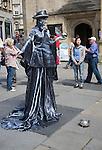 Female living sculpture performer in Abbey churchyard, Bath, Somerset, England