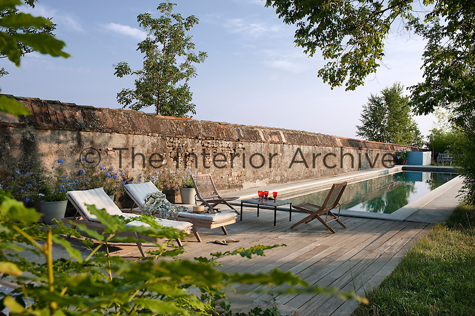 The secluded swimming pool is situated In the shelter of one of the ancient walls of La Chiesuola and simple wooden decking has been used to create an elegant seating area