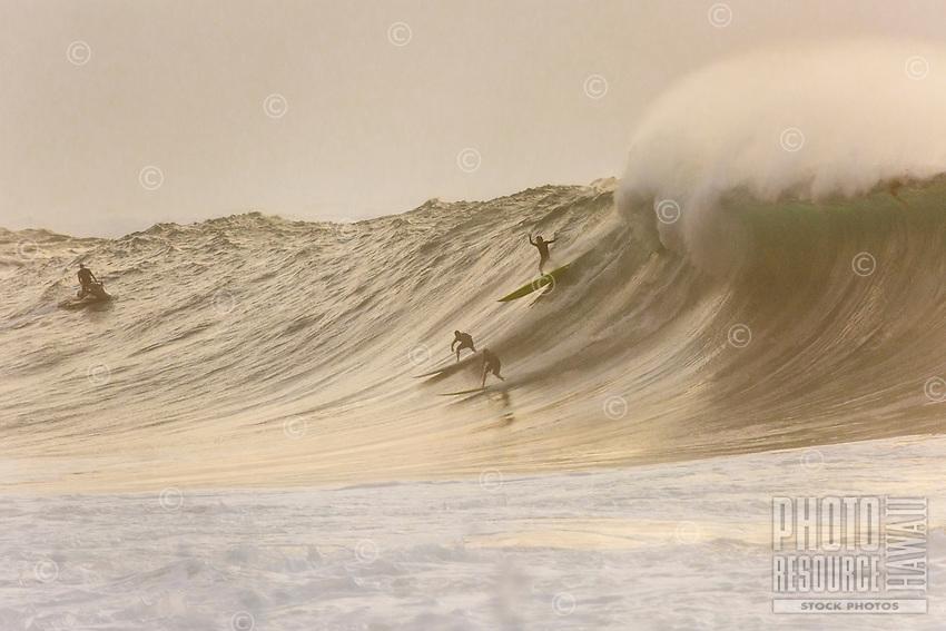 At sunset, surfers drop into a huge wave at Waimea Bay, North Shore, O'ahu.