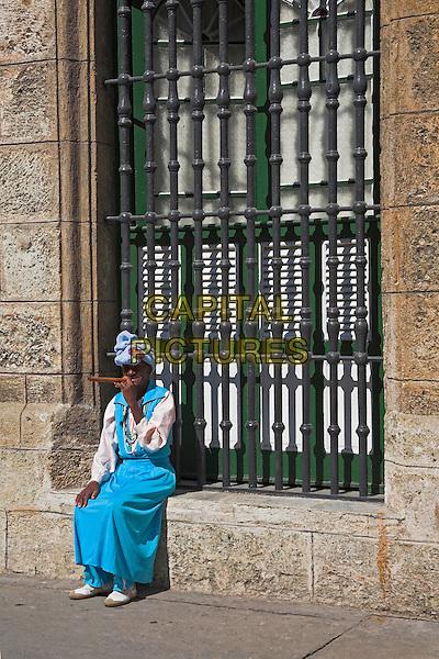Lady wearing colourful traditional clothing, smoking a cigar, Havana, La Habana Vieja, Cuba