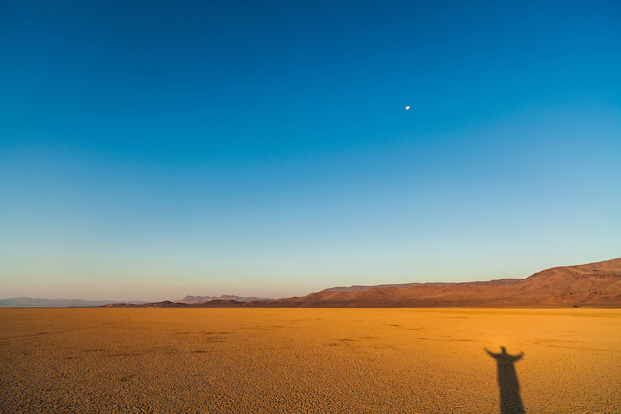 The shadow of a tall man creeps eerily across the cracked playa of the Alvord Desert in Southeast Oregon as the moon looms above.