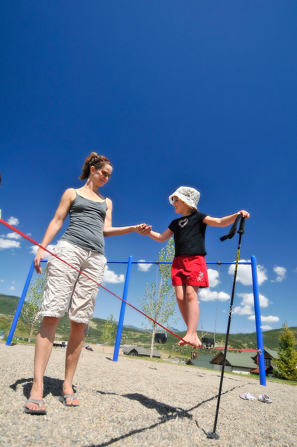 Young girl balancing on slackline on neighborhood playground with help from aunt mother, Steamboat Springs, Colorado