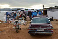 LEBANON Beqaa valley, Deir el Ahmad, camp for syrian refugees, family in tent made from old cinema poster, in front old german Mercedes Benz car / LIBANON Bekaa Tal, Deir el Ahmad, Camp fuer syrische Fluechtlinge am Dorfrand, Familie im Zelt aus alten Kinoplakaten