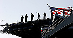 Gary Wilcox/staff... 03/23/07-- The aft flag flows in the breeze as sailors stand on the flight deck of the USS John F. Kennedy to man the rails for the final time during the ship's decommissioning ceremony last Friday, at Naval Station Mayport.