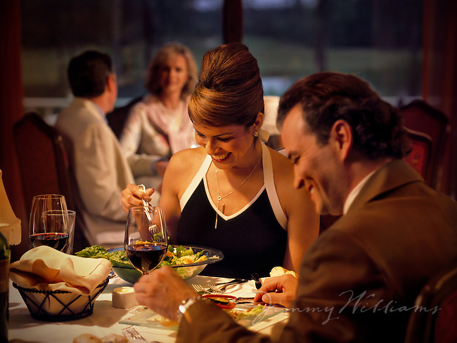 A couple dines inside of a luxurious restaurant at a Country Club & Golf resort
