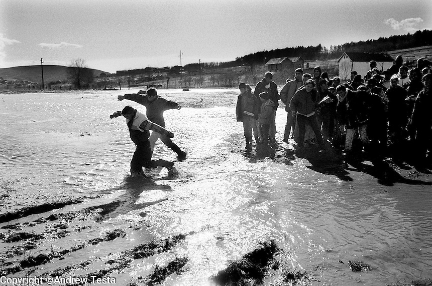 Albanians wade through a river to get to a ceremony to mark the first anniversary of the massacre of KLA fighter Adem Jashari and his family at Prekaz. 06/03/99.