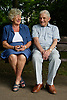 Older couple sitting on a bench in the park chatting,