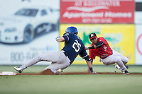 Sam Hilliard (25) of the Asheville Tourists is tagged out by Kannapolis Intimidators shortstop Johan Cruz (20) at Kannapolis Intimidators Stadium on May 26, 2016 in Kannapolis, North Carolina.  The Tourists defeated the Intimidators 9-6 in 11 innings.  (Brian Westerholt/Four Seam Images)