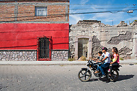 A family on a motorbike drive by Old and new facads, Jerez, Zacatecas, Mexico