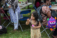 Children enjoying the party during Queen Elizabeth II birthday celebrations at the Barking Community Centre in East London. A young girl blows bubbles.