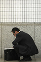 Apr. 30, 2010 - Tokyo, Japan - A Japanese businessman opens his briefcase in a street of Tokyo, Japan, on April 30, 2010. Japan's unemployment rate rose to 5.0 % in March, up 0.1 percent from the previous month, the Health, Labor and Welfare Ministry said in a report on Friday. The number of jobless people rose 150,000 from a year earlier to 3.5 million, the ministry said.