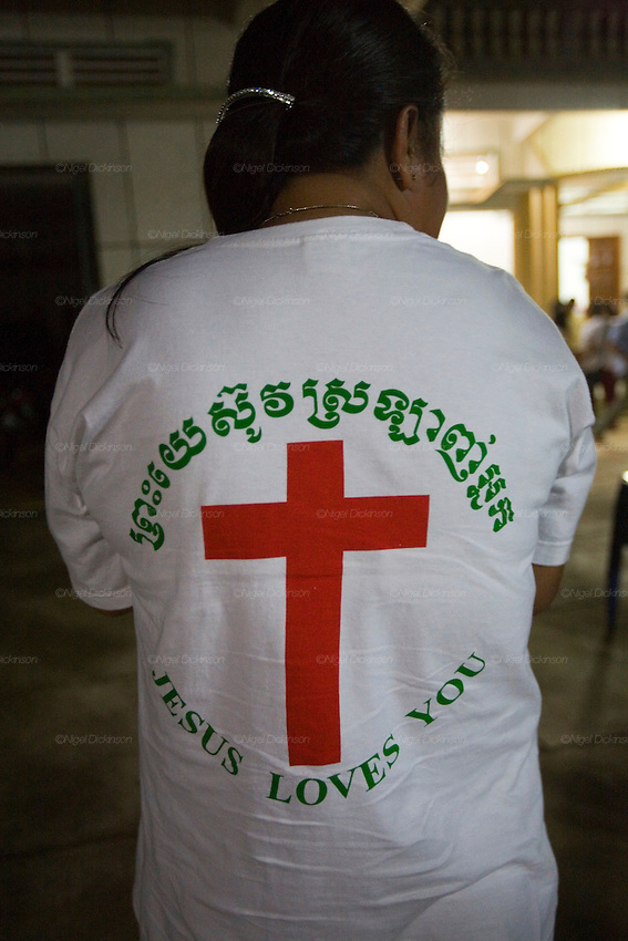 """EVANGELISM AMERICAN STYLE. South East Asia. Battambang, Cambodia. A 'University of Nations' project, registered in Cambodia as a project of the international Christian Evangelical 'Youth With a Mission' (YWAM), run by 'Group Leader' Garth Gustafson. It is a fanatical Evangelist youth movement who use english and sports teachings as a vehicle, together with religious indocrination, to turn buddhist youth and even monks, towards the Christian Bible. Garth preaches quasi-religeous sermons about 'hot and cold' climate types, of Western moral superiority and stronger work ethics, American right obsessions with family and personal responsibility, versus """"primitive people who use smiles to hide their lies"""". They preach they """"want to see your (Cambodian) nation change to be a good nation, to glorify God"""" but YWAM is a cult-like organisation with right wing and facism roots. The YWAMers force themselves upon AIDS patients in local hospitals, looking for the very sick and dying, offering neither drugs nor food, but instead, prayers about Christian redemption, offer everlasting life, which when rejected by buddhists, they are accused of being """"bitter"""" for declining them.///'Youth With a Mission' (YWAM) in exultation and prayer during an evening worship in Battambang. Slogan: Jesus loves you"""