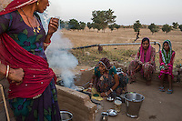 Guar farmer Kelavati Devi (centre), 38, makes tea for her family after a hard day's work in their field in Rajera village, Bikaner, Rajasthan, India on October 23, 2016. Non-profit organisation Technoserve works with farmers in Bikaner, providing technical support and training, causing increased yield from implementation of good agricultural practices as well as a switch to using better grains better suited to the given climate. Photograph by Suzanne Lee for Technoserve
