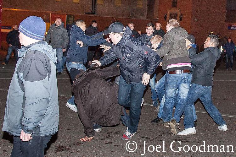"© Joel Goodman - 07973 332324 . 23/02/2012 . Manchester , UK . A man whips another with a belt as rival Manchester United and Ajax fans fight outside Old Trafford stadium ahead of the match . A large number of police contain about 150 travelling Ajax fans and lead them on foot through Manchester and Salford to Old Trafford , closing roads to traffic as they go . The fans chant ""Amsterdam hooligans"" as they go . This ahead of Manchester United hosting Ajax Europa at Old Trafford in the UEFA cup . Photo credit : Joel Goodman"