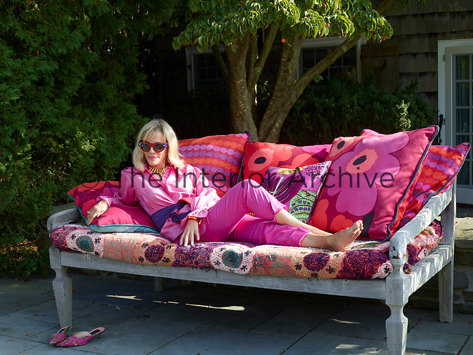 A portrait of designer Lorry Newhouse relaxing on the patio.