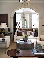 A large archway separates the double living room and a spatial illusion is created by the mirror placed between the two windows